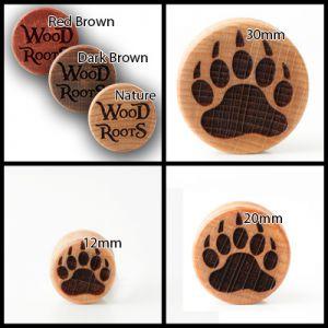 Eine Kollage von Bildern mit Plugs darauf. Es sind vier Bilder zu sehen, eines mit den unterschiedlichen Farben der Holzplugs und die anderen vier mit unterschiedlichen Größen des Plugs mit dem Motiv einer Bärentatze.